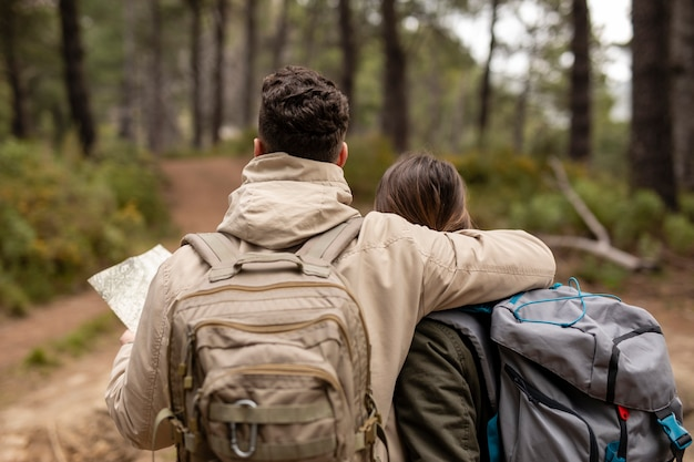 Vista traseira pessoas com mochilas na natureza
