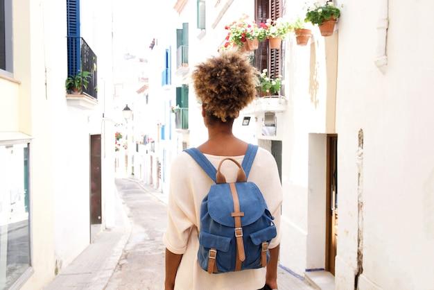 Vista traseira, retrato, de, mulher americana africana, andar, ligado, rua, com, saco