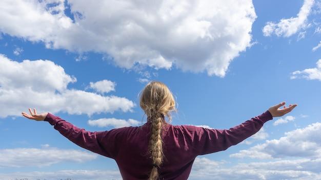 Vista traseira. retrato de uma mulher que estica seus braços ao ar livre em direção ao céu.