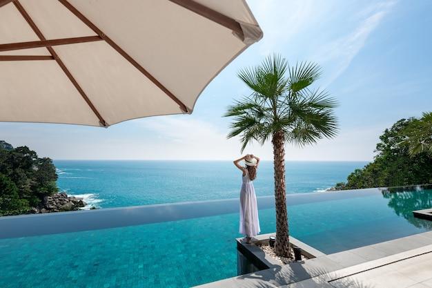 Vista traseira: senhora de luxo em um vestido branco e chapéu posando perto de uma palmeira à beira de uma piscina sem fim