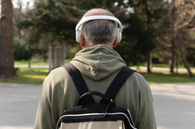 Vista traseira sênior ouvindo música em um fone de ouvido