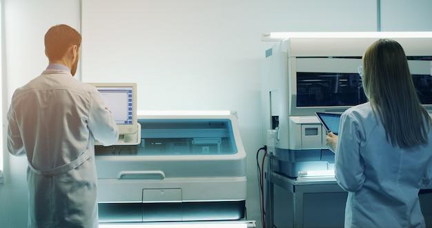 Vista traseira sobre os cientistas médicos masculinos e femininos caucasianos trabalhando no laboratório no computador e tablet. traseira.