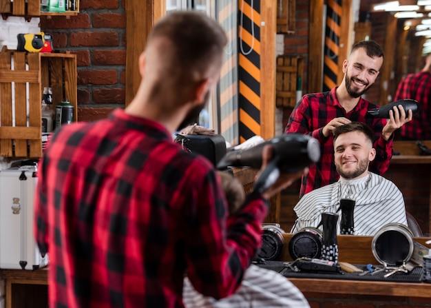 Vista traseira sorridente barbeiro usando secador de cabelo