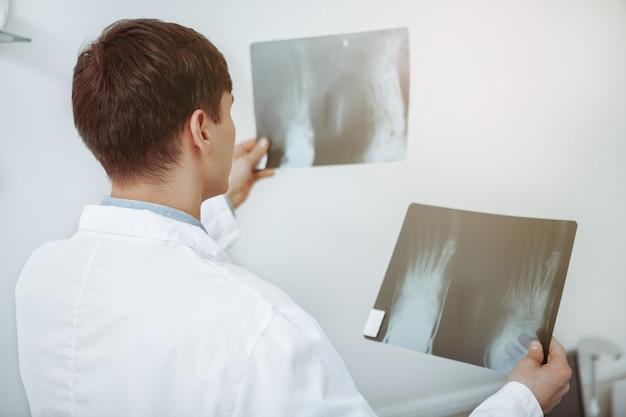 Vista traseira, tiro, de, um, irreconhecível, doutor masculino, comparar, dois, raios x, varreduras, de, um, paciente