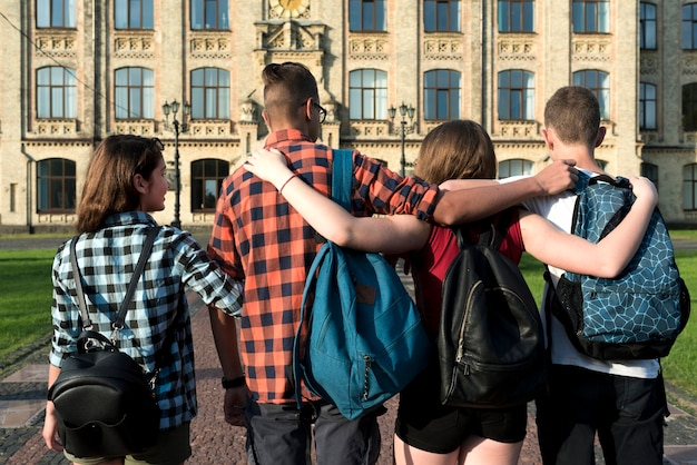 Vista traseira, tiro médio, de, abraçando, adolescentes, ir escola secundária