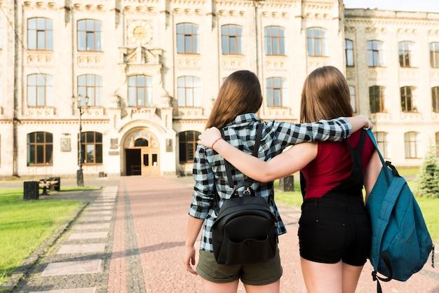 Vista traseira, tiro médio, de, dois, meninas adolescentes, abraçando
