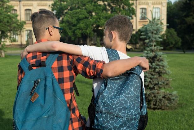 Vista traseira, tiro médio, de, dois, meninos adolescentes, abraçando