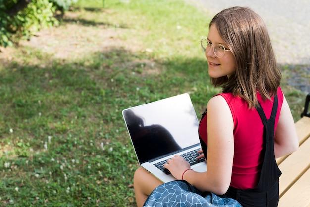 Vista traseira, tiro médio, de, menina escola, usando computador portátil