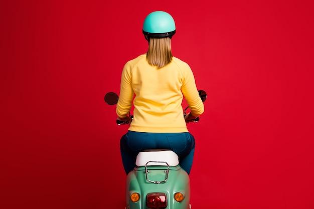 Vista traseira traseira da garota sentada na motocicleta dirigindo na parede vermelha