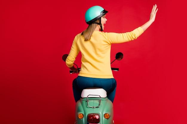 Vista traseira traseira de uma garota alegre dirigindo um ciclomotor acenando com a mão na parede vermelha