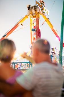 Vista traseira turva casal no parque temático
