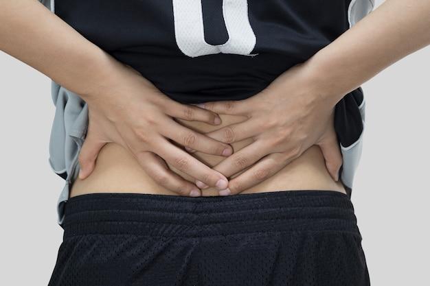 Vista traseira - um jovem segurando as costas em dor