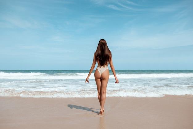 Vista traseira: uma senhora sensual e magra, com cabelos molhados, vestindo biquíni da moda e de pé no mar contra as ondas enquanto relaxa o mar. férias tropicais