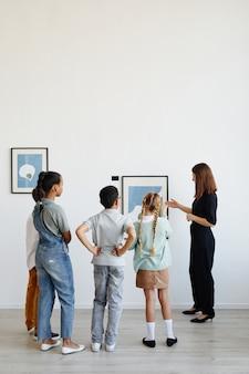 Vista traseira vertical em um grupo diversificado de crianças ouvindo uma guia turística feminina durante uma visita à galeria de arte moderna