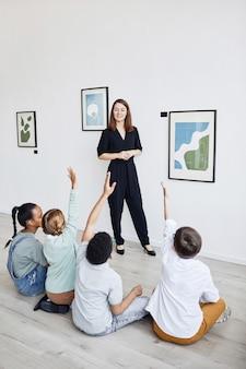 Vista traseira vertical para um grupo diversificado de crianças sentadas no chão em uma galeria de arte moderna ouvindo um especialista em arte