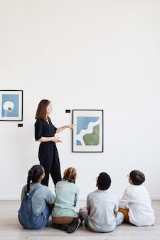 Vista traseira vertical para um grupo diversificado de crianças sentadas no chão na galeria de arte moderna e olhando pinturas, copie o espaço