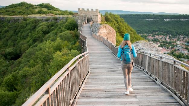 Vista traseira viajante andando pela ponte