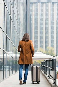 Vista traseira viajante com bagagem