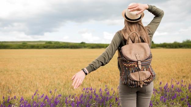 Vista traseira viajante com chapéu e mochila