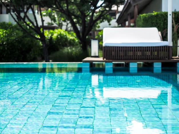 Vista turva da piscina com espreguiçadeira branca no resort.