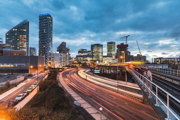Vista urbana com arranha-céus, trem turva e trilhas de semáforo