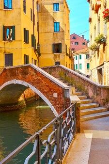Vista veneziana com ponte em um pequeno arco sobre o canal, veneza, itália
