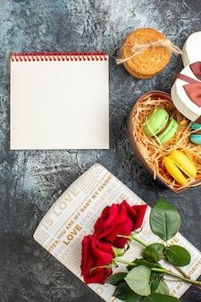 Vista vertical da bela caixa de presente em forma de coração com deliciosos macarons e biscoitos, caderno espiral rosa vermelha em fundo escuro glacial