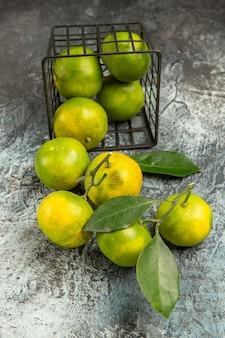 Vista vertical da cesta caída com tangerinas verdes frescas cortadas ao meio e tangerina descascada em fundo cinza