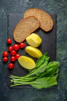 Vista vertical de batatas frescas descascadas e fatias de pão dietético tomate verde pacote na tábua de madeira no verde preto mistura cores backgound
