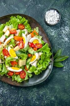 Vista vertical de deliciosa salada caseira com muitos ingredientes em um prato e sal sobre fundo preto de mistura verde