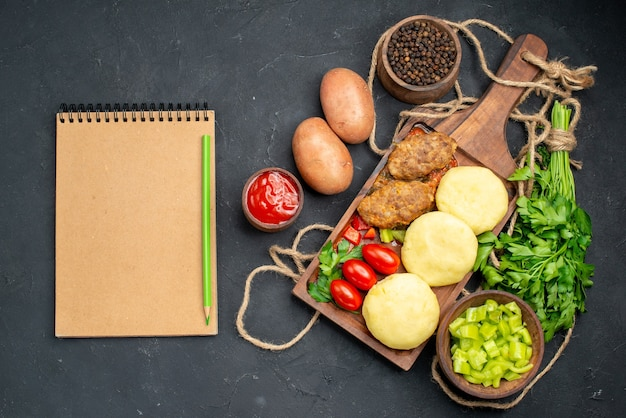 Vista vertical de deliciosas costeletas de vegetais picados um monte de verdes para o jantar e caderno Foto gratuita