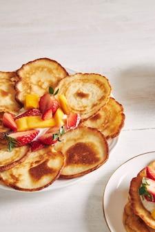 Vista vertical de deliciosas panquecas com frutas em uma mesa de madeira branca