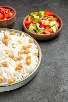 Vista vertical de ervilhas temperadas e arroz para o jantar e chucrute e salada na mesa preta