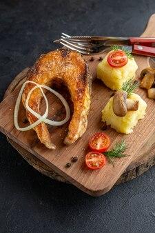 Vista vertical de farinha de peixe frito com cogumelos, vegetais, queijo e talheres em uma placa de madeira na superfície preta angustiada