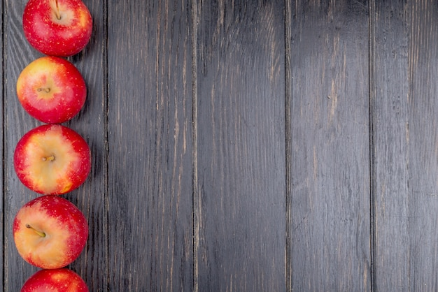 Vista vertical de maçãs vermelhas no lado esquerdo e fundo de madeira com espaço de cópia
