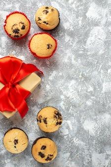 Vista vertical de pequenos cupcakes - presentes de natal com fita vermelha no lado direito na superfície do gelo