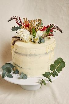 Vista vertical de um delicioso aniversário de flores brancas em creme no topo do bolo com uma gota na lateral