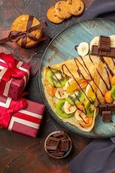 Vista vertical de um delicioso crepe servido com frutas cítricas picadas, decorado com calda de chocolate e caixas de presente em cores diferentes