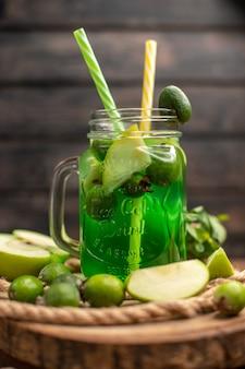Vista vertical de um delicioso suco de fruta servido com maçã e feijoas em uma tábua de madeira sobre uma mesa marrom