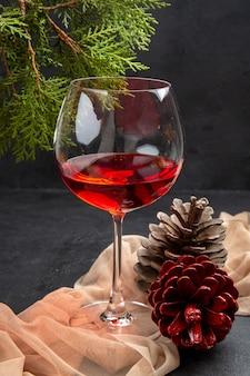 Vista vertical de um delicioso vinho tinto em uma taça de vidro na toalha e cones de coníferas de ramos de abeto em um fundo escuro