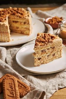 Vista vertical de um pedaço de bolo de biscoito de lótus delicioso com caramelo com biscoitos na mesa
