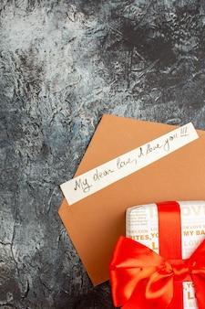 Vista vertical de uma caixa de presente lindamente embalada, amarrada com uma fita vermelha em um envelope e uma carta de amor em um fundo escuro de gelo