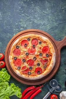 Vista vertical de uma deliciosa pizza caseira na tábua de madeira, tomate, molho verde de ketchup na superfície escura