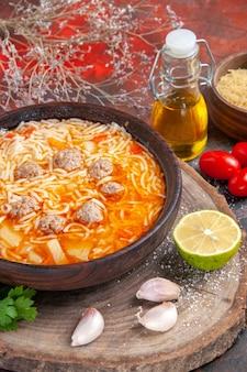 Vista vertical de uma deliciosa sopa de macarrão com frango em uma garrafa de óleo de verduras de madeira, alho, tomate e limão em fundo escuro