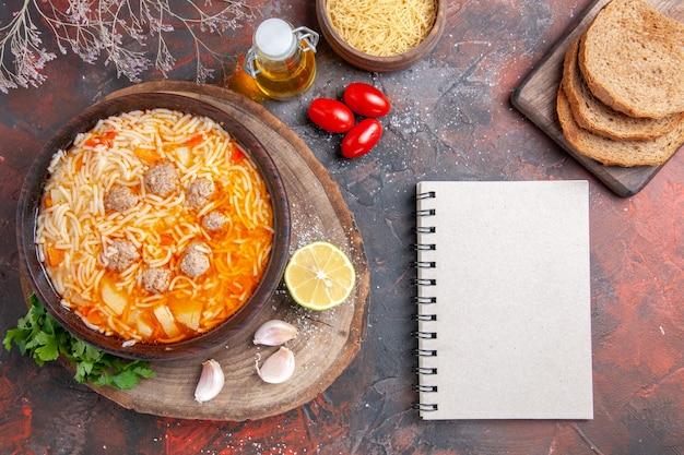 Vista vertical de uma deliciosa sopa de macarrão com frango na garrafa de óleo de tary de madeira, alho, limão, tomate e caderno em fundo escuro