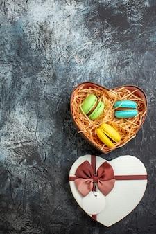 Vista vertical de uma linda caixa de presente em forma de coração com deliciosos macarons no lado esquerdo em um fundo escuro e gelado