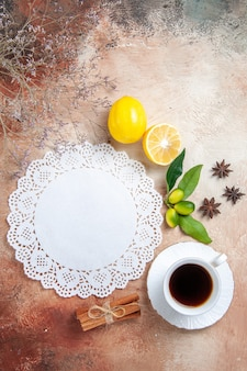 Vista vertical de uma xícara de chá, guardanapo de limão e chá preto colorido