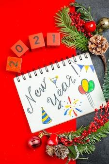 Vista vertical do caderno espiral com escrita de ano novo e acessórios de decoração de desenhos ramos de abeto xsmas números de meias em um guardanapo vermelho e árvore de natal em fundo escuro