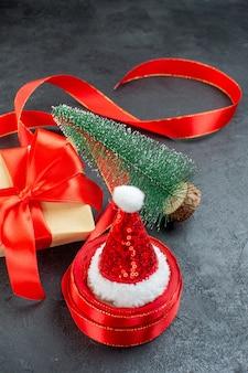 Vista vertical do chapéu de papai noel em um rolo de fita e um lindo presente de árvore de natal em fundo escuro