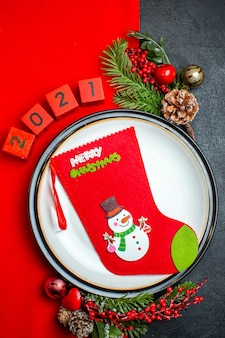 Vista vertical do fundo do ano novo com a meia de natal no prato de jantar acessórios de decoração ramos de abeto e números num guardanapo vermelho sobre uma mesa preta